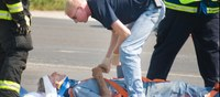image of EMS worker helping injured person.